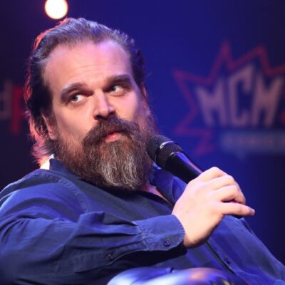 David Harbour wears a dark shirt and leans back as he holds a microphone onstage