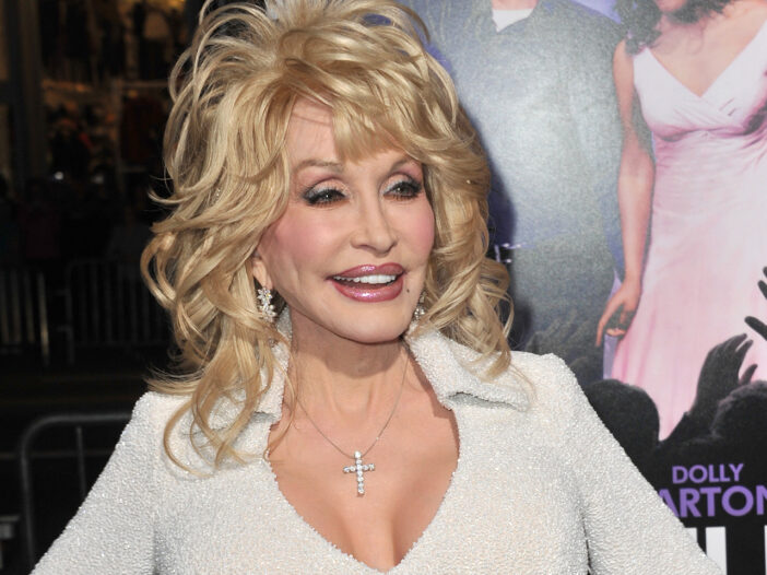 Dolly Parton smiling in a low-cut dress.