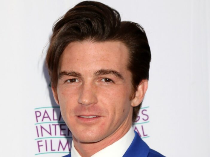 Drake Bell wears a blue suit against a blue background