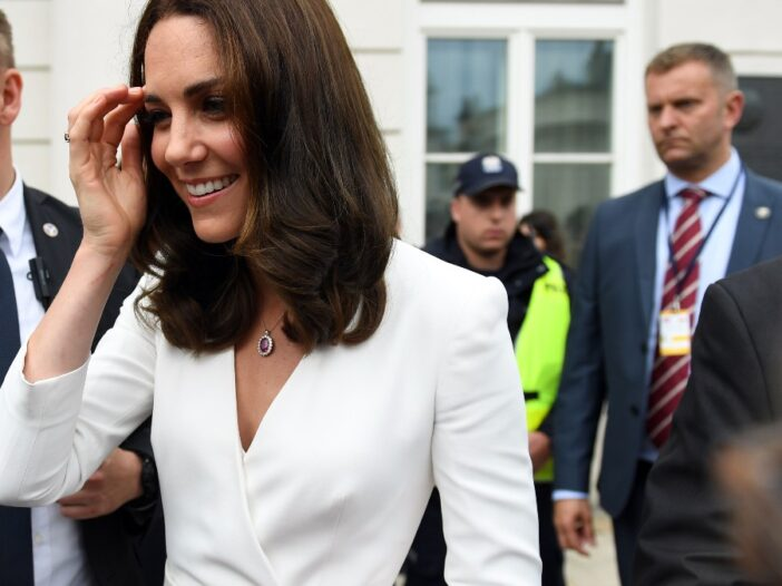 Kate Middleton wears a white dress as she greets a crowd while surrounded by security