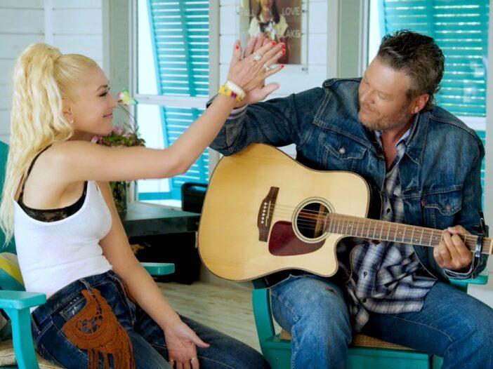 Gwen Stefani, in a white tank top, high fives Blake Shelton, in a blue jean jacket