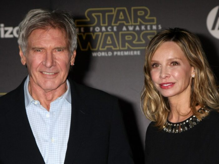 Harrison Ford wears a dark suit and stands with wife Calista Flockhart, in a black dress, on the red carpet