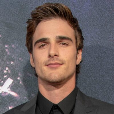 Jacob Elordi wears a dark suit with a black shirt on the red carpet