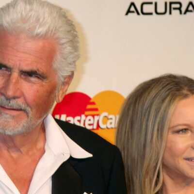 James Brolin, in a black suit, stands with Barbra Streisand, in a black gown, on the red carpet