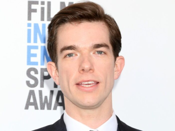 John Mulaney wears a dark suit against a white background on the red carpet