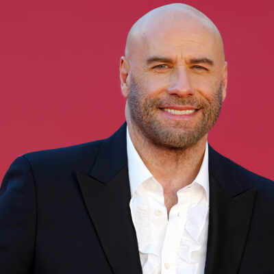 John Travolta smiling in front of a red background