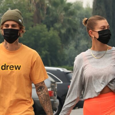 Justin Bieber wears a yellow shirt and strolls hand in hand with wife Hailey, in a gray shirt and orange shorts