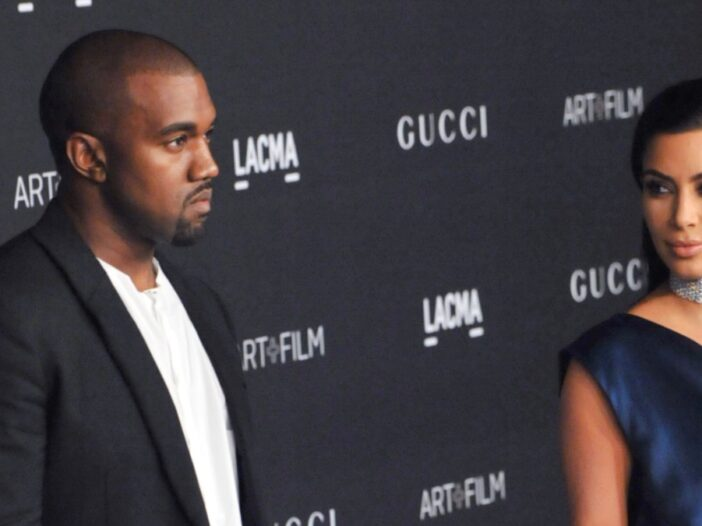 Kanye West wears a dark suit and stands slightly apart from estranged wife Kim Kardashian, in a blue dress