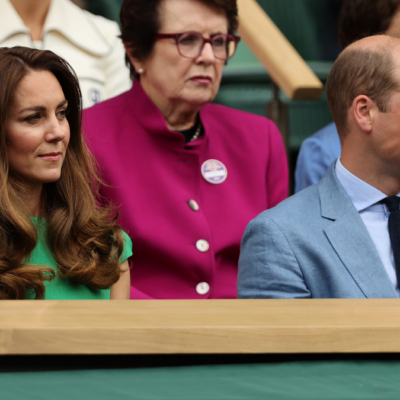 Kate Middleton, in a green dress, sits with Prince William, in blue suit, in the stands at Wimbledon