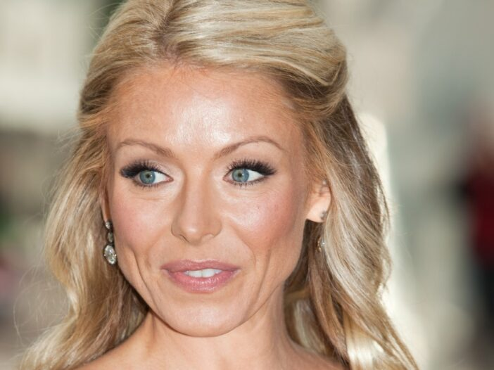 Kelly Ripa wears a strapless blue gown against a blurry background