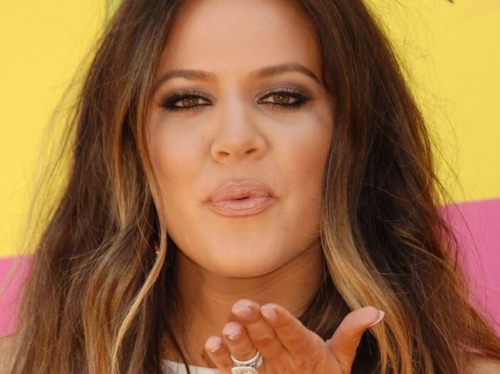 Khloe Kardashian blows a kiss in front of a yellow and pink background