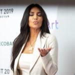 Kim Kardashian in all white, blowing a kiss