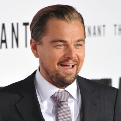 Leonardo DiCaprio laughs while wearing a dark suit on the red carpet