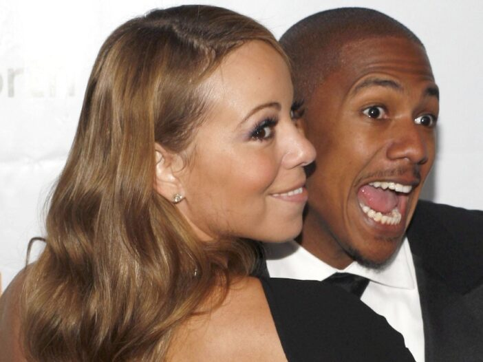 Mariah Carey, in a black dress, cozies up to then-husband Nick Cannon, in a black tux, on the red carpet