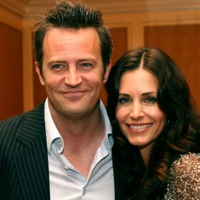 Matthew Perry wears a dark suit jacket as he poses beside Courteney Cox in a speckled green gown