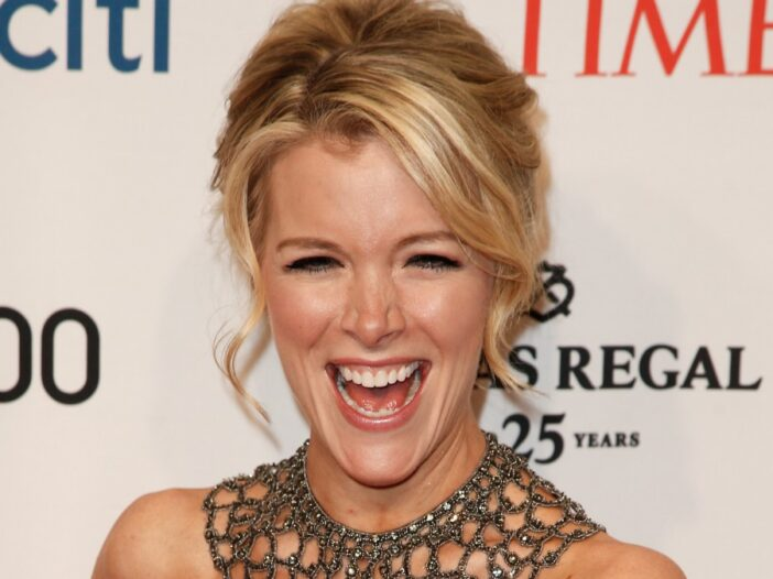Megyn Kelly laughs while wearing a blue dress on the red carpet