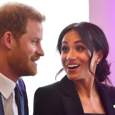 Meghan Markle on the right, looking and laughing with Prince Harry