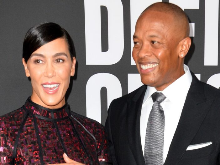 Nicole Young and Dr. Dre smile while walking the
