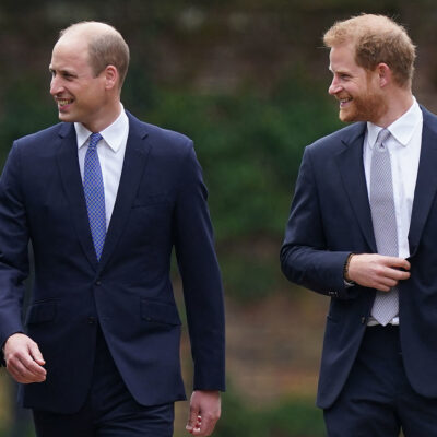 Prince William (Left), smiling and walking with a smiling Prince Harry