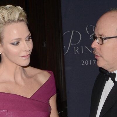 Princess Charlene wears a mauve dress and listens as Prince Albert, in a black suit, speaks