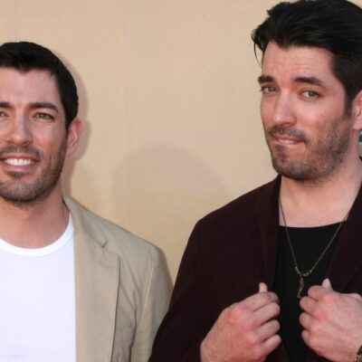Johnathan and Drew Scott pose together on the red carpet against a pale tan background