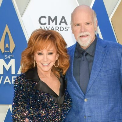 Reba McEntire wears a black dress and poses with Rex Linn, in a blue suit, on the CMA red carpet
