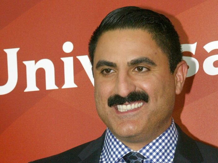 Reza Farahan wears a black suit against a deeep orange background on the red carpet