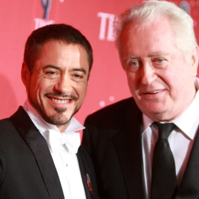 Robert Downey Jr, in a tux, stands with father Robert Downey Sr, in a black suit, on the red carpet