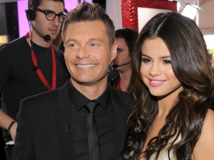 Ryan Seacrest, in a black suit, and Selena Gomez, in a gold dress, pose together at the Grammy's