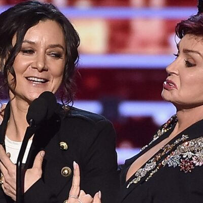 Sara Gilbert, left, and Sharon Osbourne stand together onstage as they accept an award