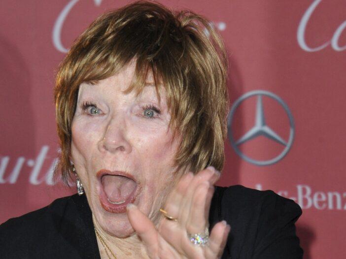 Shirley MacLaine wears a black dress and waves as she walks the red carpet
