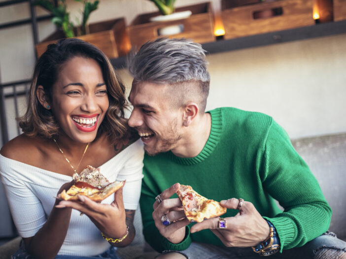 Couple eating pizza.
