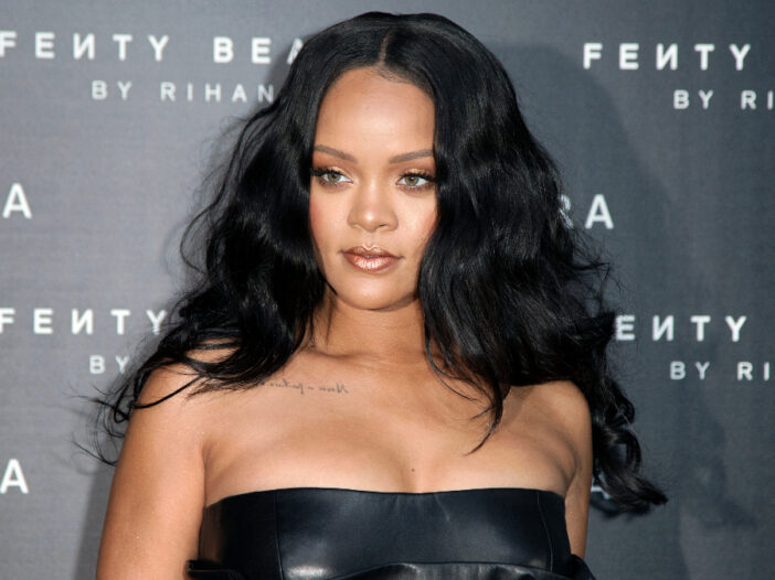 Rihanna wears a black dress in front of a grey background