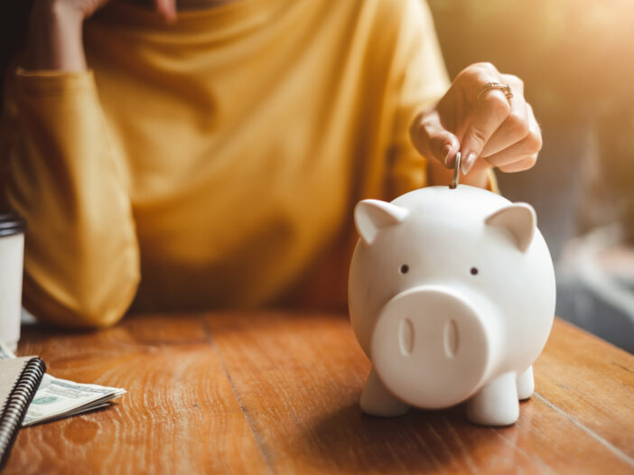 Image of woman putting money in a piggybank
