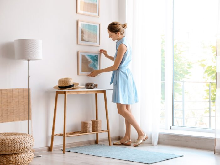 Image of woman decorating her home in a dress.