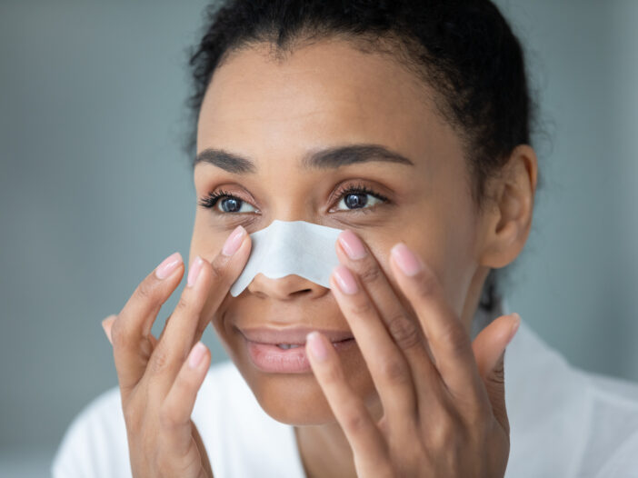 Image of a woman with a pore strip on her nose.