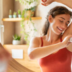 Image of woman putting on deodorant.