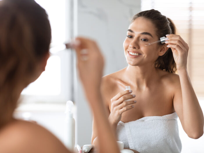 Image of woman applying serum to her face.