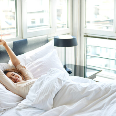 Young woman waking up in her bed.