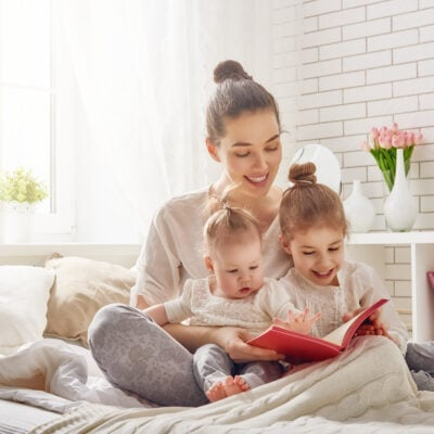 Image of a young mom reading to her kids