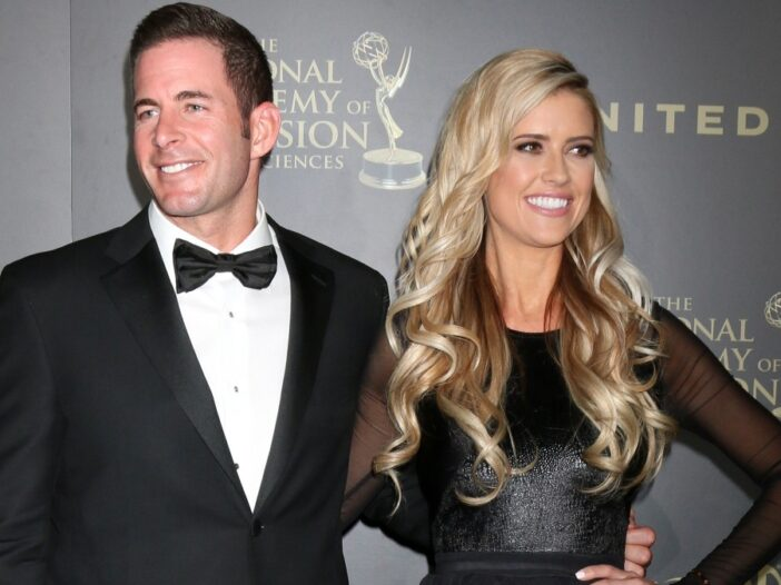 Tarek El Moussa and his now ex wife Christina Haack, both dressed in black formal wear, pose on the red carpet