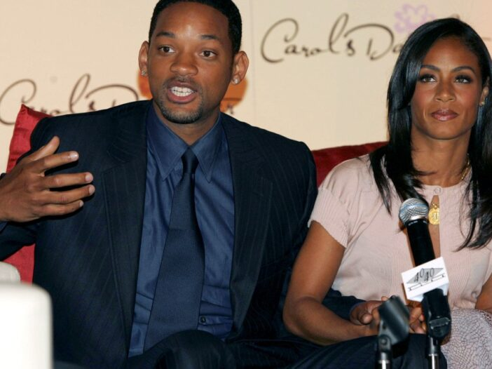 Will Smith, in a dark suit, sits with wife Jada Pinkett Smith, in a pale top