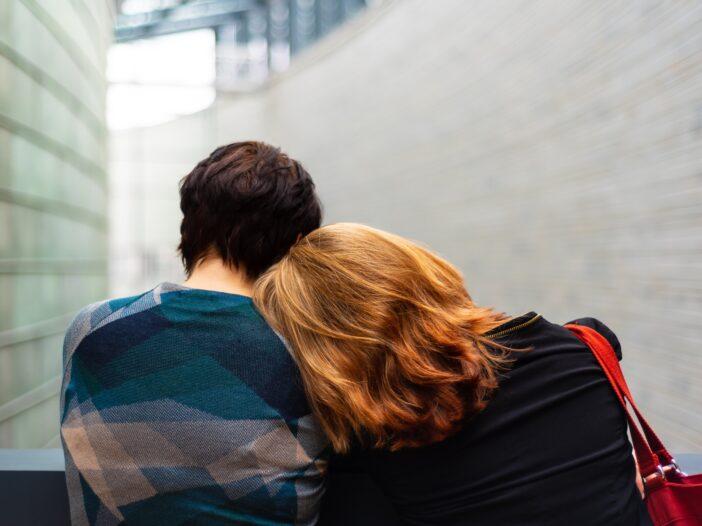 Woman leaning on friend's shoulder