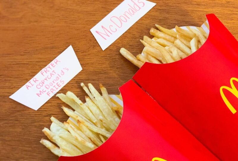 Our copycat McDonald's fries in a classic red McDonald's fry container next to the actual product.
