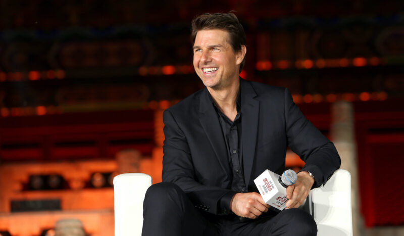 Tom Cruise smiling in a black suit holding a microphone