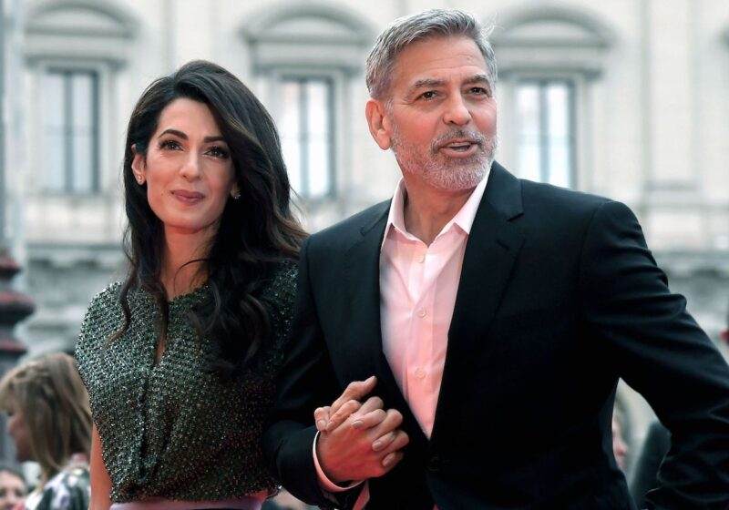 George and Amal Clooney holding hands outside