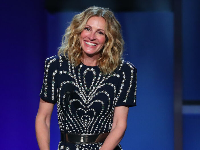Julia Roberts smiling on a stage in a black dress