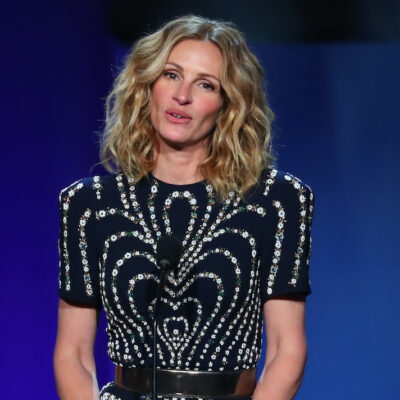 Julia Roberts speaking on stage in a black dress