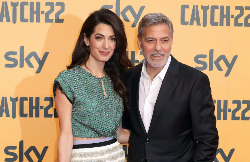 George Clooney in a black suit with Amal Clooney in a green outfit