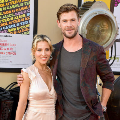 Chris Hemsworth in a red suit with wife Elsa Pataky in a peach dress